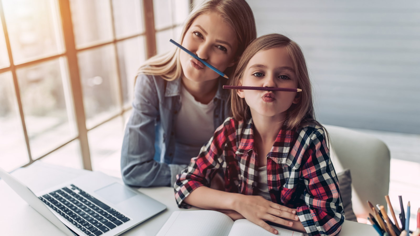 mom and daughter holding pencils with their noses