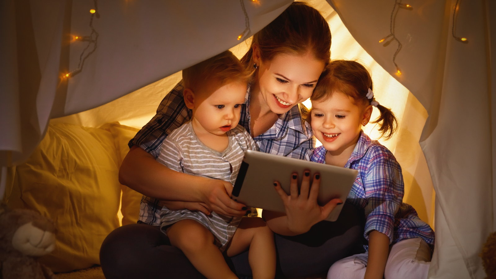 mom using tablet with young kids