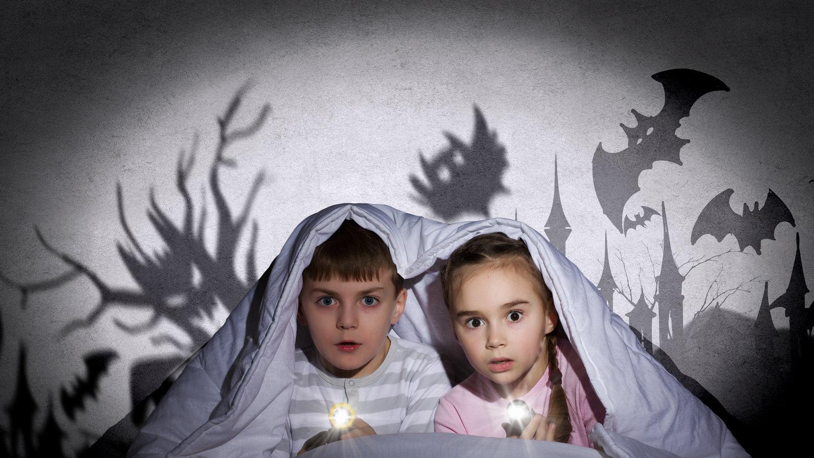 children scared underneath blanket in bed