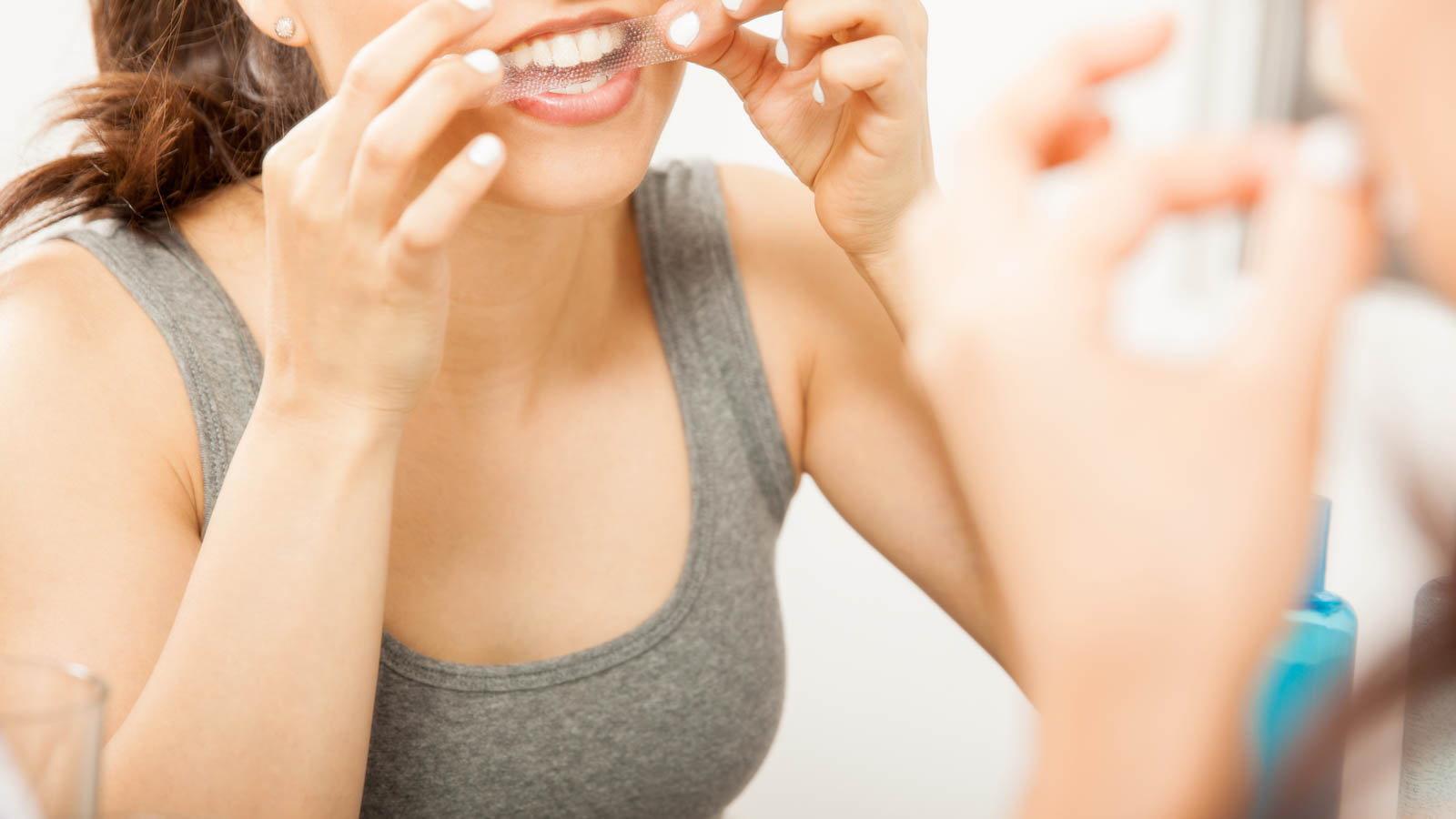 woman using a teeth whitening strip