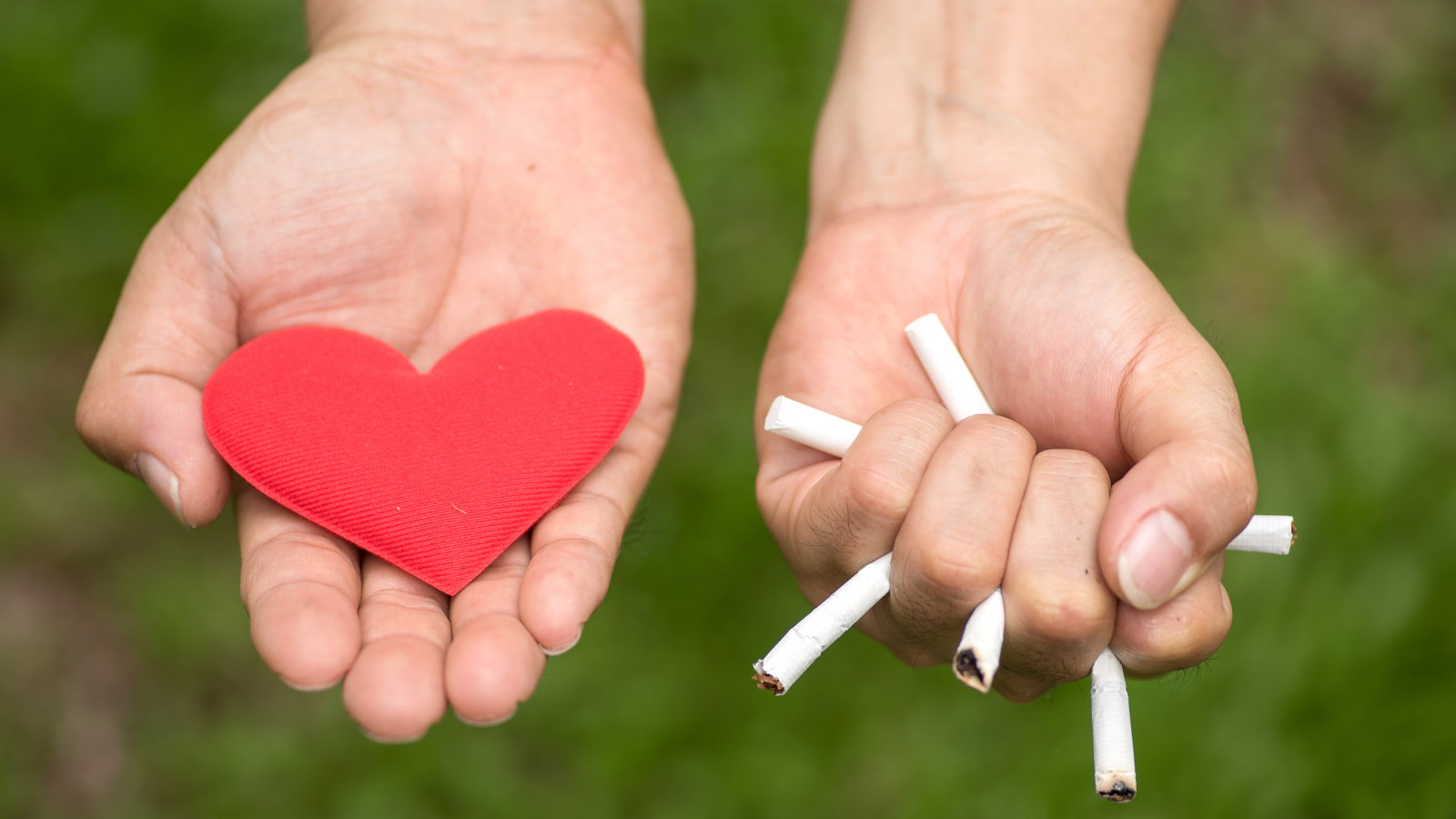 woman holding paper heart in one hand and crushed cigarettes in the other