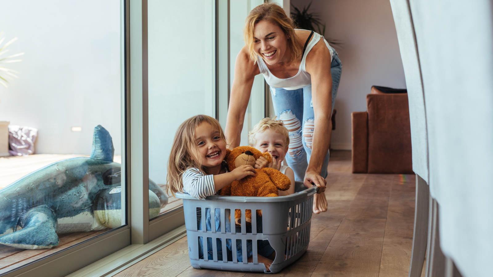 mom pushing kids around in laundry basket
