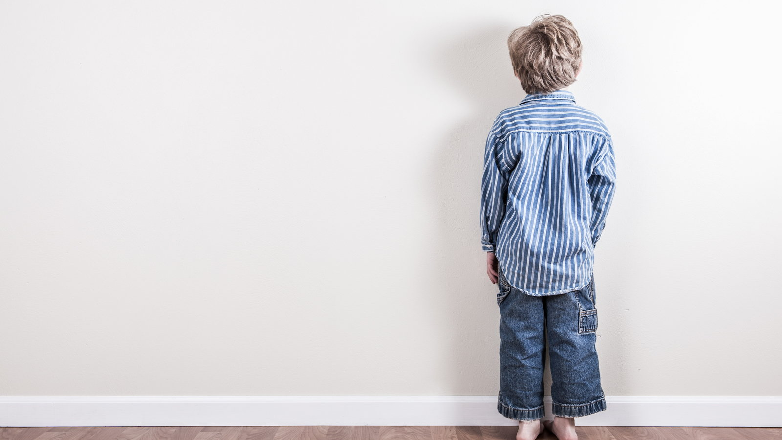 child standing at wall doing time out