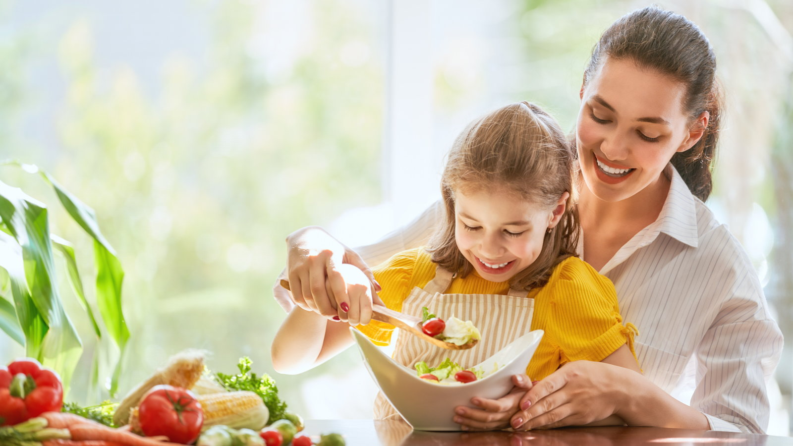 mother making salad with daughter