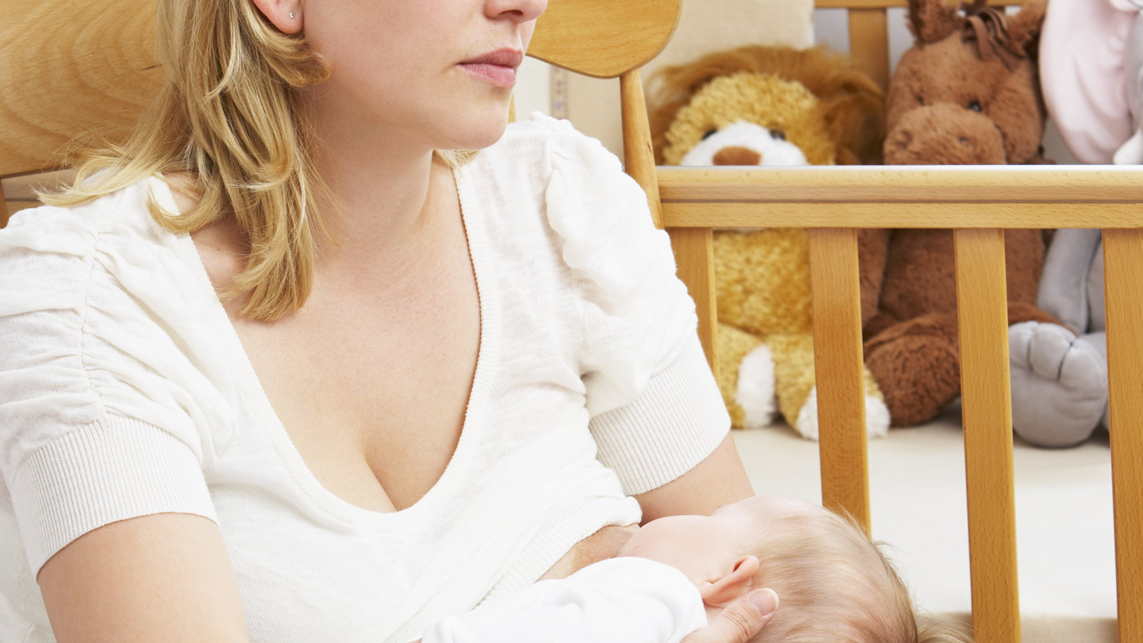 sad woman breastfeeding in rocking chair