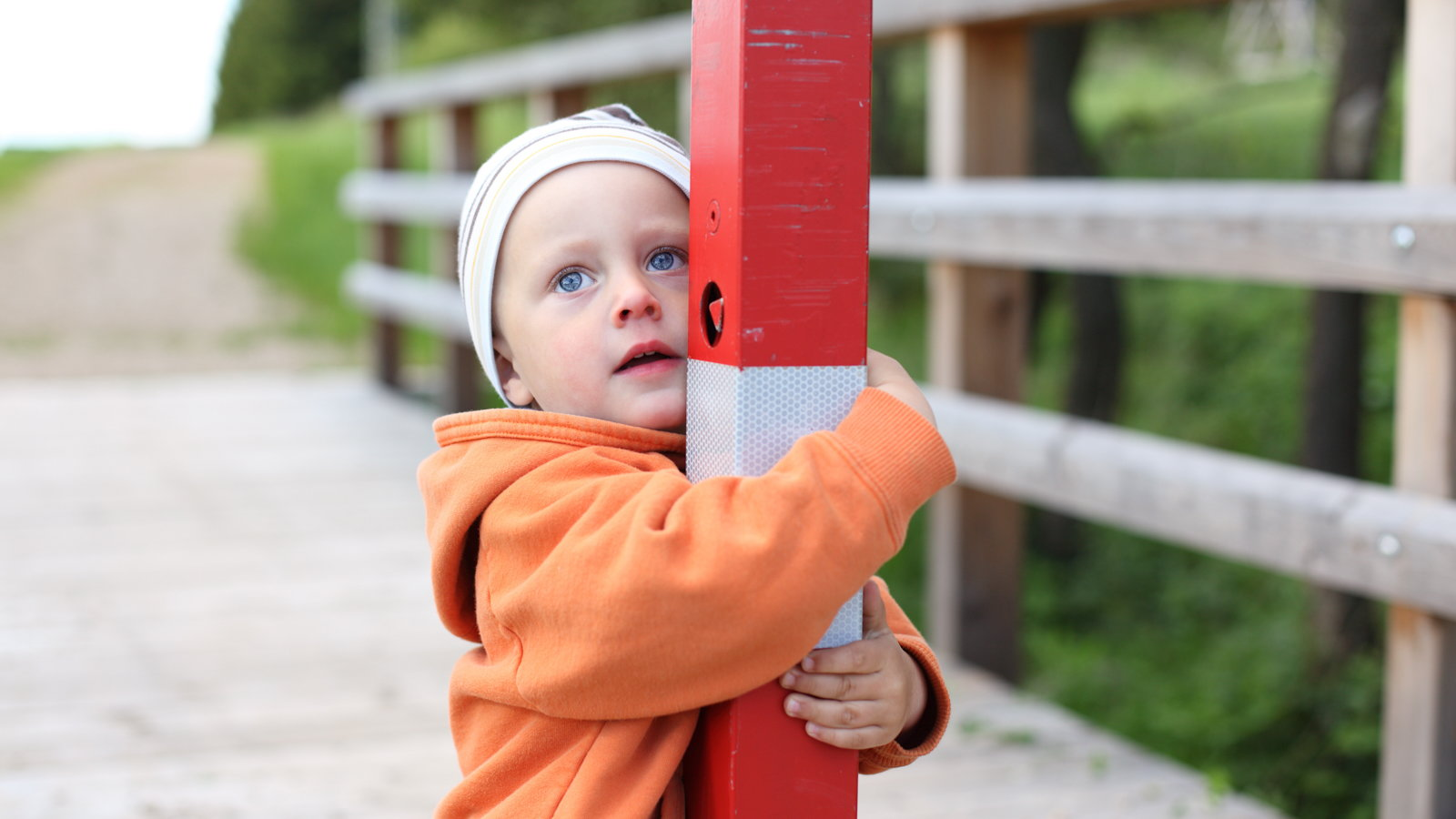 boy holding post