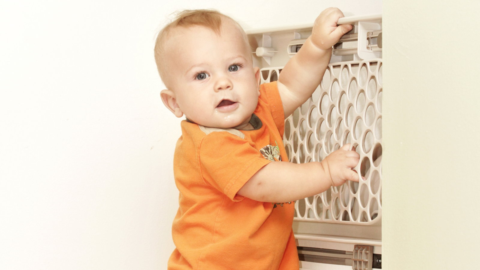 baby holding onto baby gate