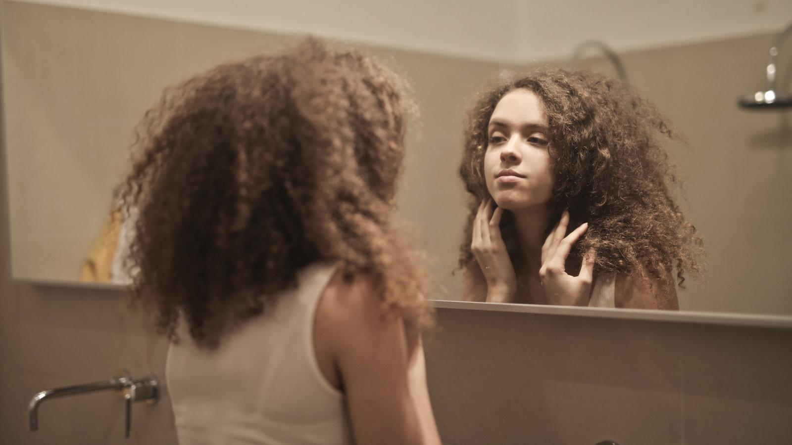 teen girl looking in the mirror