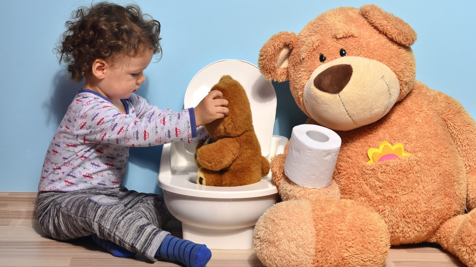 boy teaching teddy bear how to use the potty