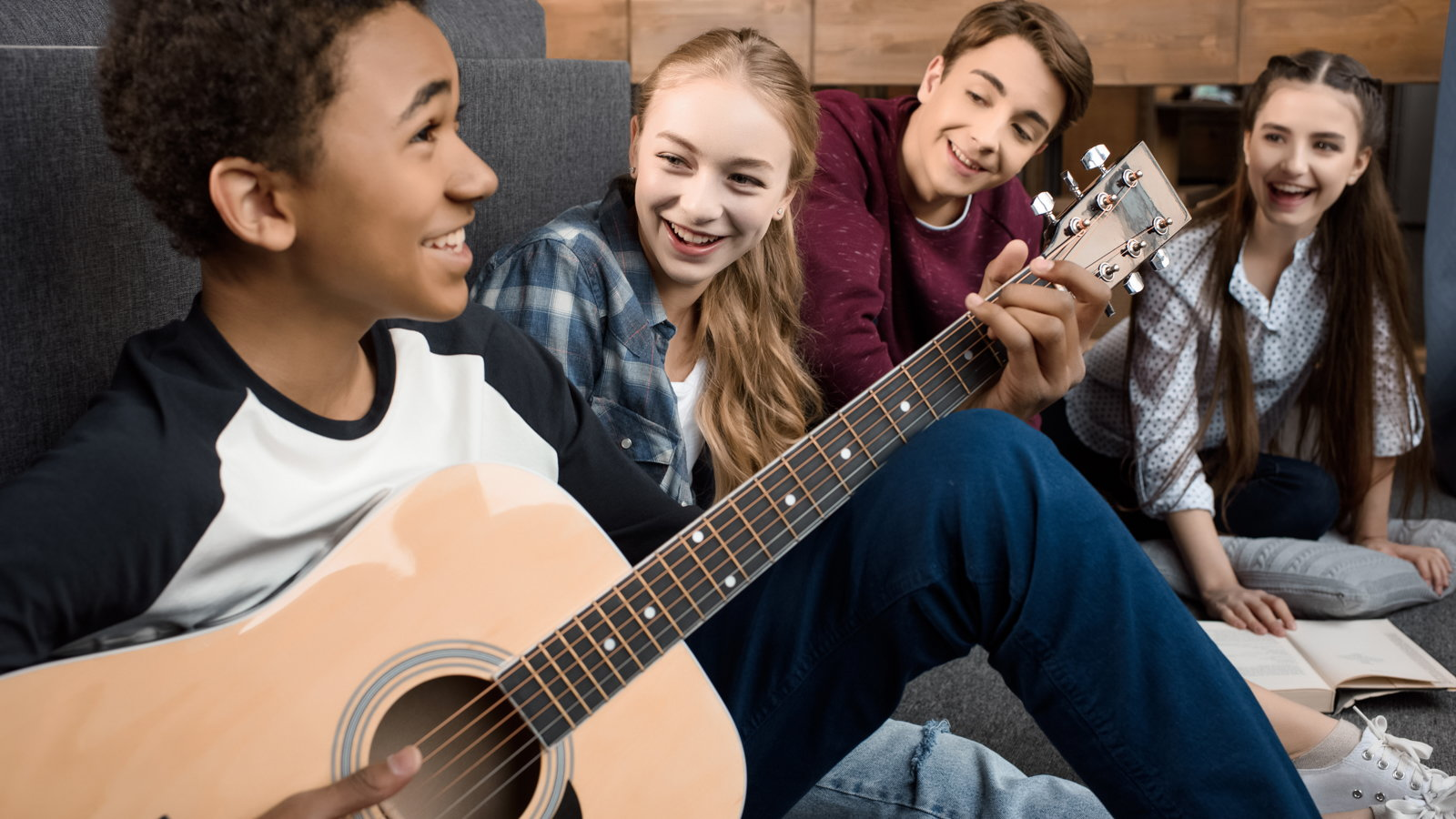 teen boy playing guitar with friends