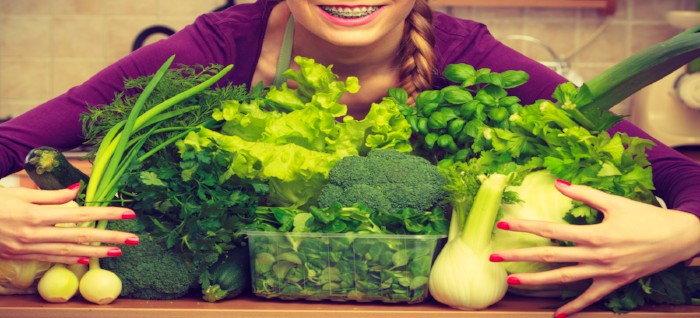 woman holding a large bundle of fall veggies