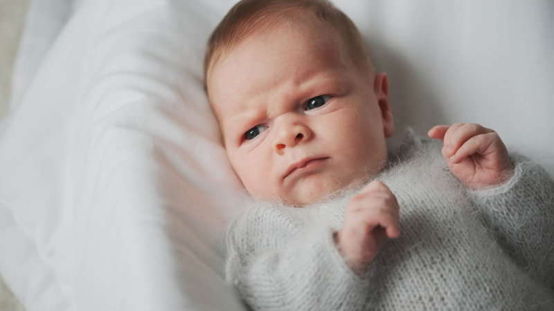 Baby wearing sweater with angry face