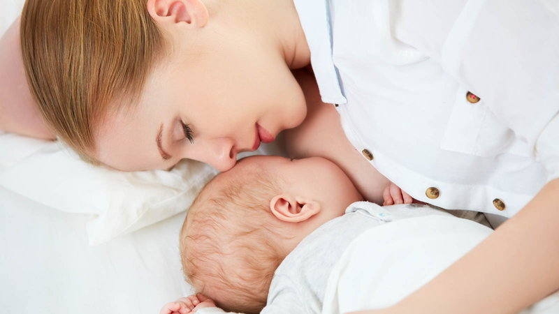 Mom breastfeeding baby while sleeping.