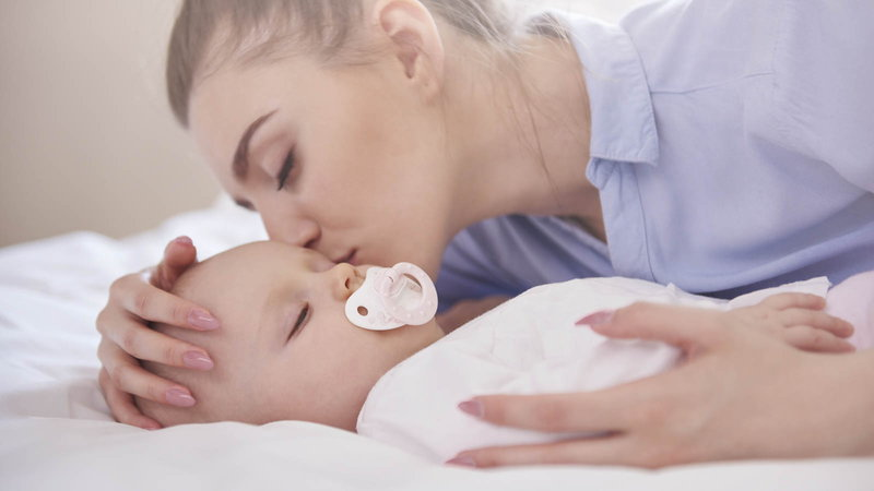 mother kissing a baby that is sucking on a pacifier