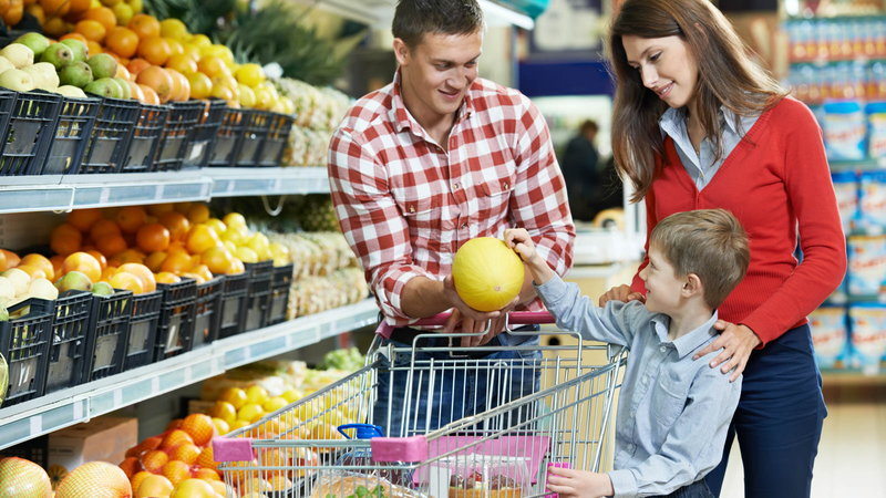 parents letting child pick out fruit at the grocery store
