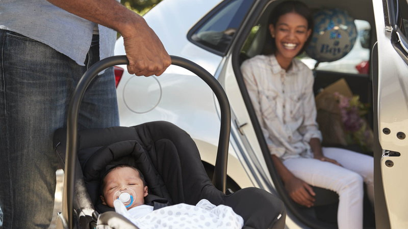 Gater holding baby in baby seat while mother watches from car
