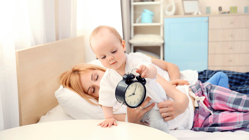 Baby holding a clock with mother on bed