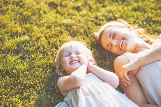 mom and daughter laughing on the grass