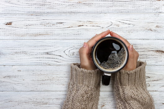 A woman warms her hands on a hot mug of coffee.