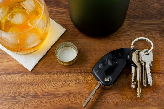 car keys next to an alcoholic beverage