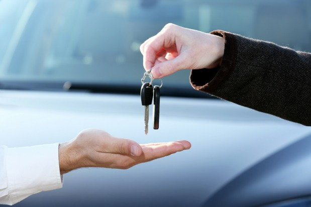 close up of hand giving set of car keys to another hand