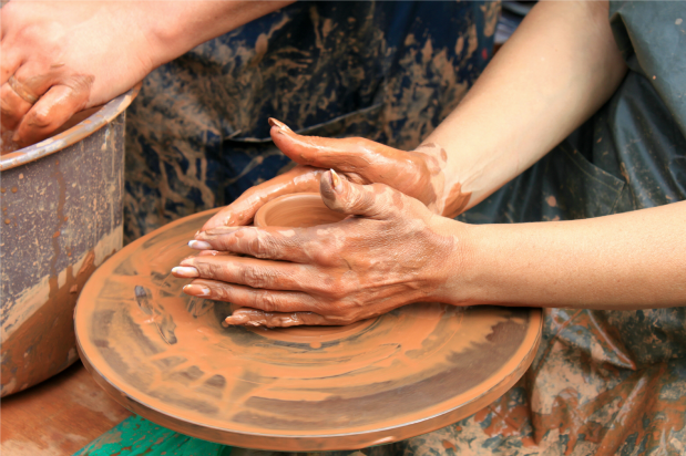 close up of hands drenched in clay while doing pottery work