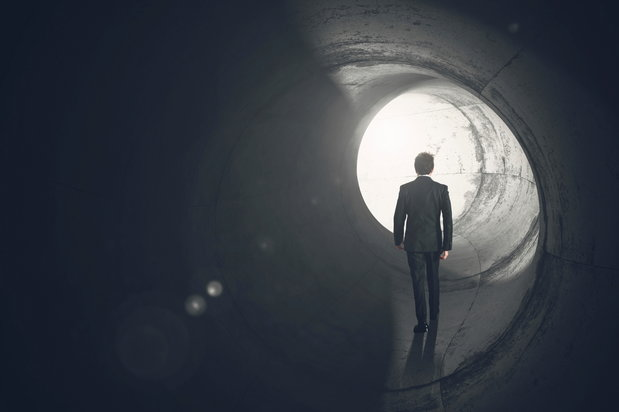 man walking to light at end of tunnel