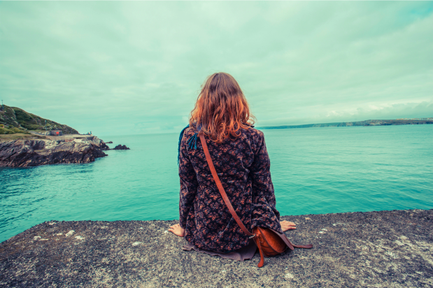 woman sitting alone by the ocean