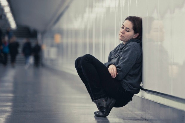 depressed woman sitting and leaning on a wall