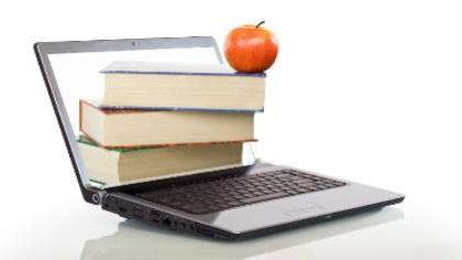 An open laptop balances a stack of a books and an apple.