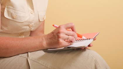A woman writing in her planner.