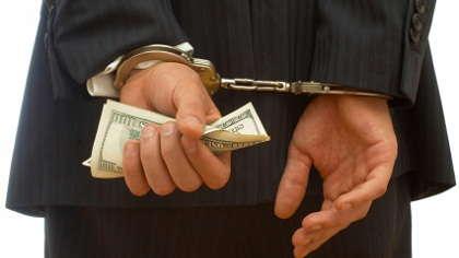 Man in cuffs holding money.