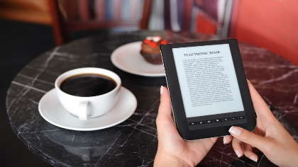 A woman reads an electronic book in a coffee shop.