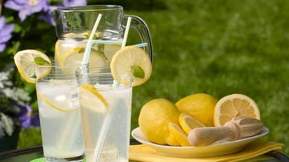 Glasses of lemonade and a plate of lemons.
