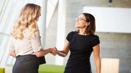 A business handshake between 2 women.