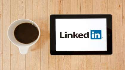 A tablet with LinkedIn and a cup of coffee.
