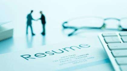 A business handshake over a resume.