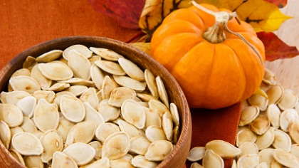 A bowl of baked pumpkin seeds sitting next to a small pumpkin.