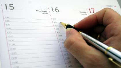 A hand writes in a commitment on a calendar.