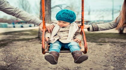 A toddler in a swing between parents.