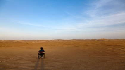 A lone person sitting in the middle of the desert.