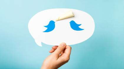 A hand holds up a speech bubble with Twitter birds tweeting.