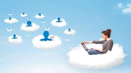A woman sits on a cloud with a laptop.