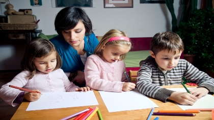 A woman watches over three children who are coloring pictures on paper.