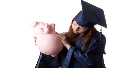 A graduate holding her piggy bank upside down.