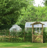 Timber garden arch and handmade hardwoodgatewith cleft sweet chestnut rail fence