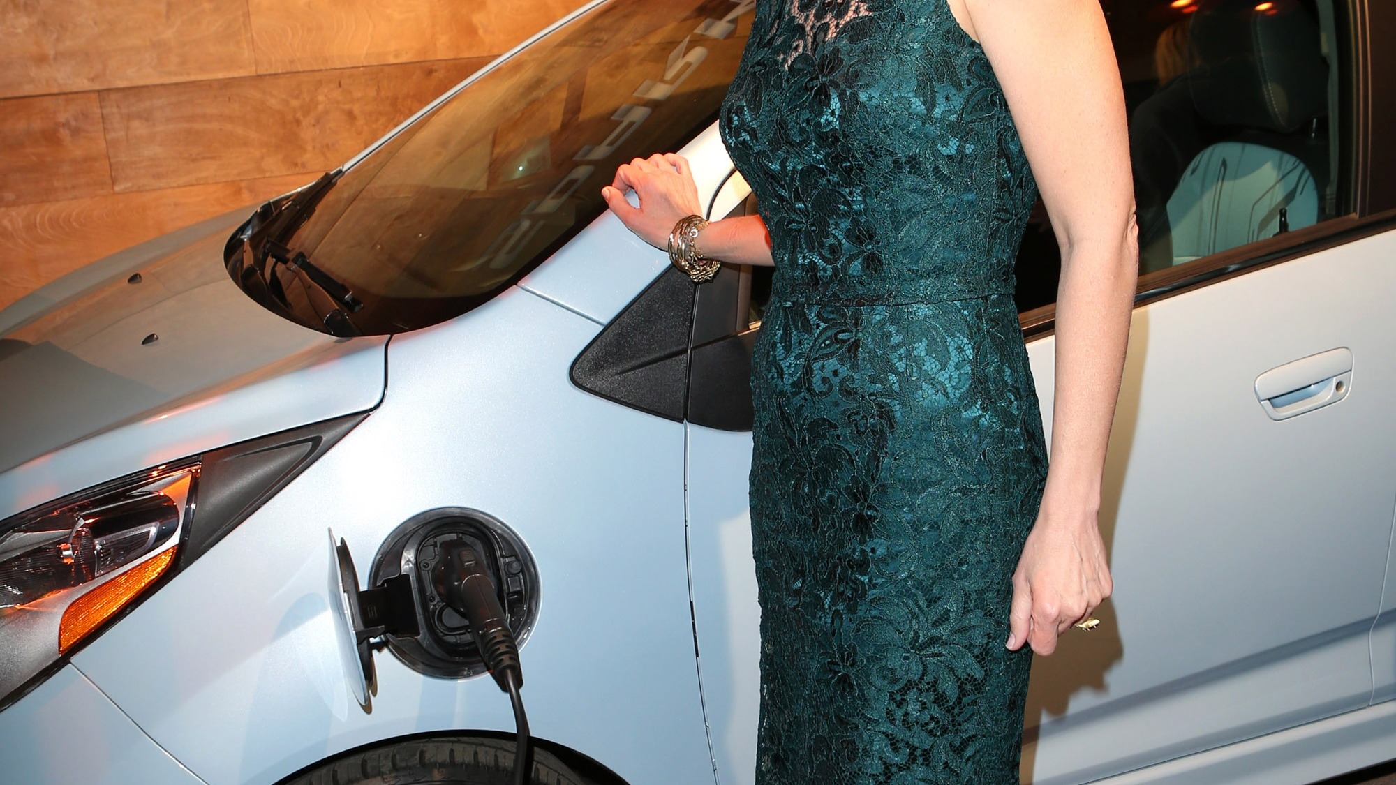 Helen Hunt poses with a Chevy Spark EV at the pre-Oscar event