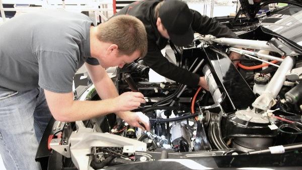 Tesla Model S workshop - technicians working under the hood of VIN # 8