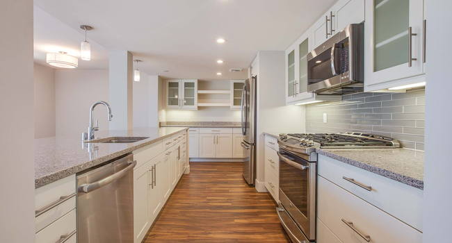 Kitchen with spacious, quartz countertops, stainless steel appliances, frosted glass cabinets, and soft-close drawers